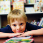 Photo of boy leaning his chin on his hands while sitting at a library table with books behind him