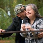 Couple with developmental disabilities kissing on bridge