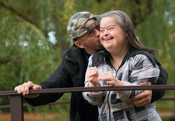 Couple with developmental disabilities kissing on bridge