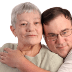 Adult son hugging aging mother
