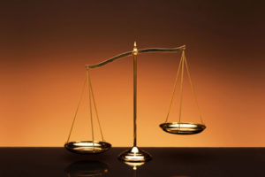 Golden brass balance or imbalance scale on orange color background.