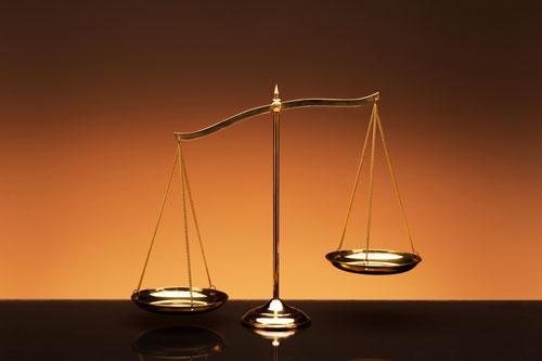 Golden brass balance or imbalance scale on orange color background.