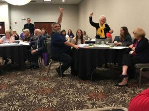 New board members standing and holding up hands to be recognized during elections