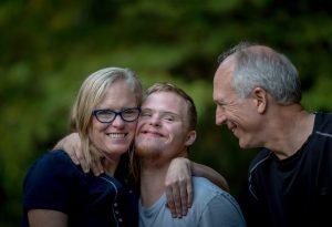 الأم والأب والابن البالغ يتعانقون ويبتسمون
