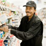 Image of man reaching for cans on grocery store shelf