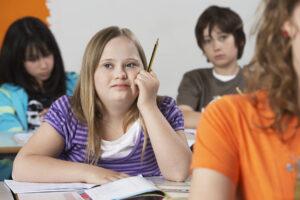 Молодая девушка сидит за партой с карандашом в руке и одноклассники вокруг нее.